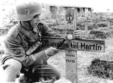 Un divisionario clava la cruz en la tumba de un camarada